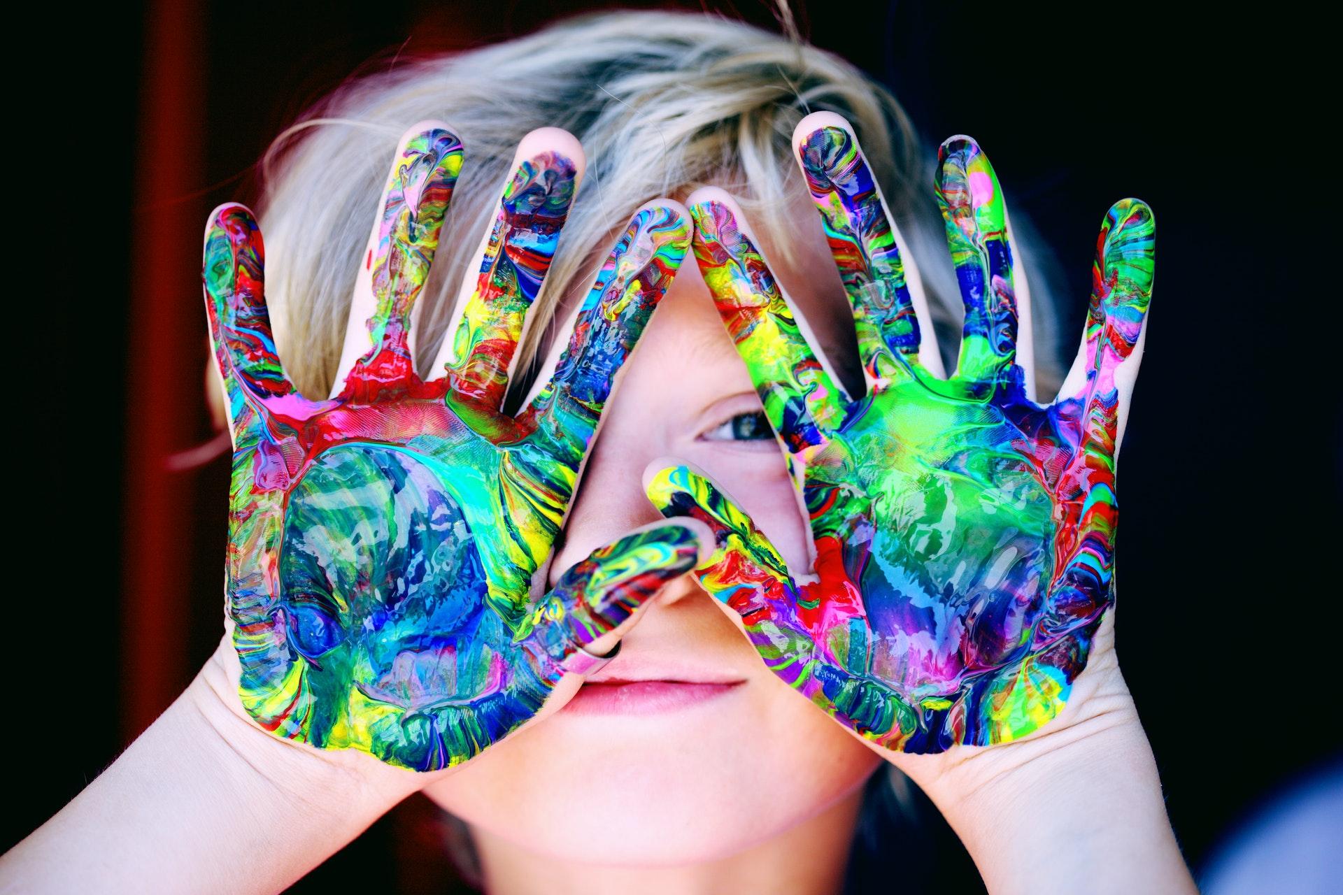 Header: Ett barn som håller händerna - fulla med färg - framför ansiktet