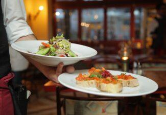 En servitör håller fram två tallrikar med mat