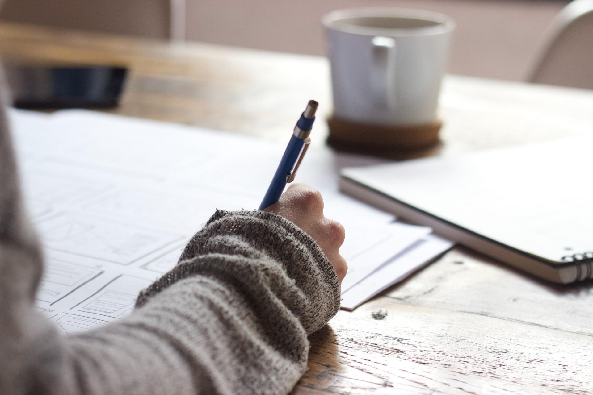 En person skriver något på ett papper.