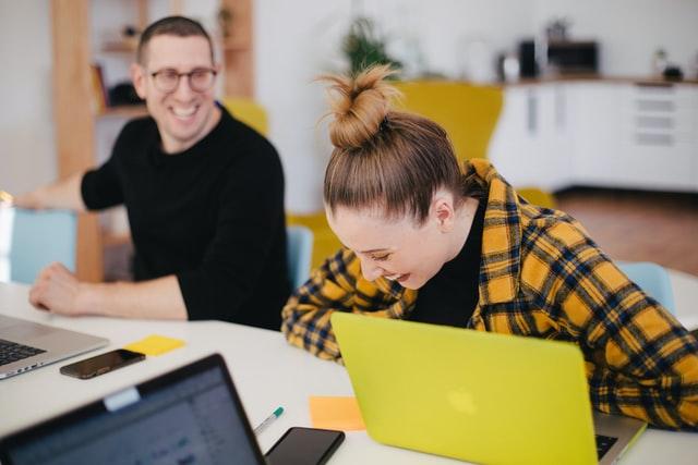 Två personer skrattar tillsammans framför laptops